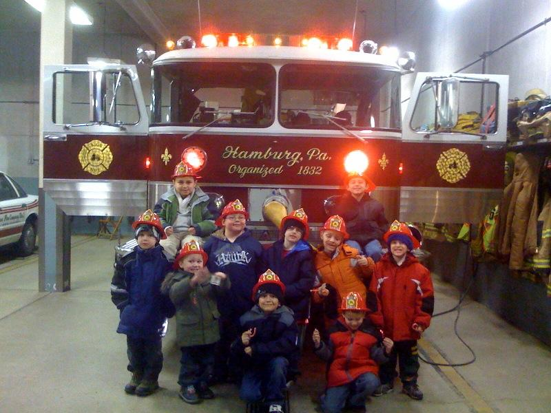 Tiger Scouts showing off their new fire helmets, sitting on the bumper of Engine 61-1.