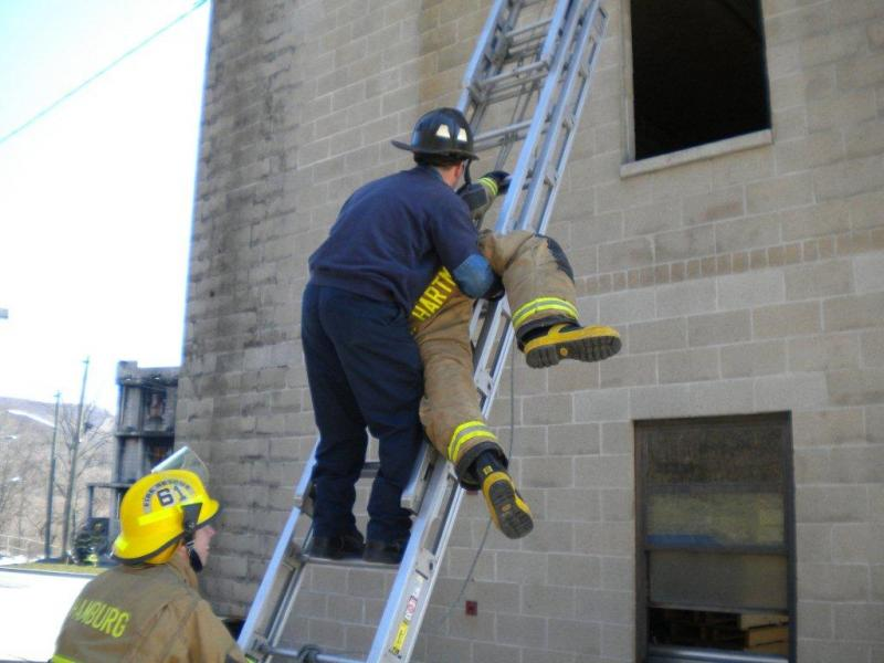 Instructor Reinert demonstrating how to bring an unconcious victim down a ladder