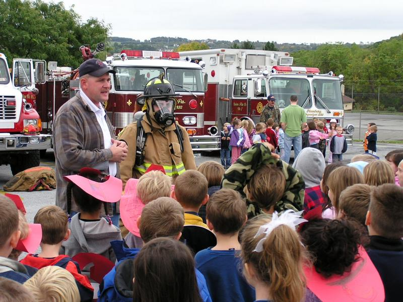 Chief Hatt shows the children what a fully equipped firefighter looks like, and explains that they shouldn't be afraid.