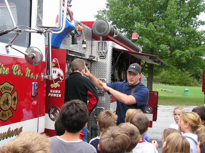 Eric Trubilla shows the children the gauges on the pump panel.