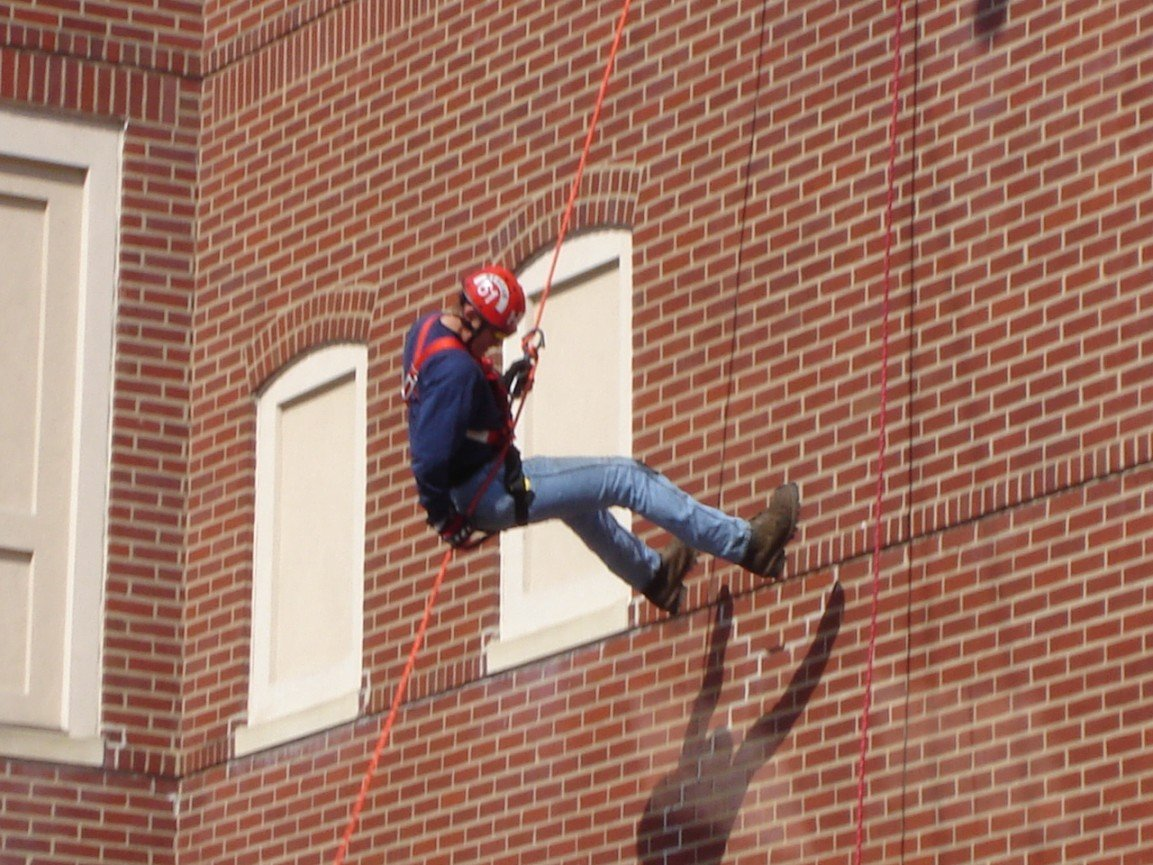 Firefighter Matt Bechtel rappels down the side of the school during the demonstration.