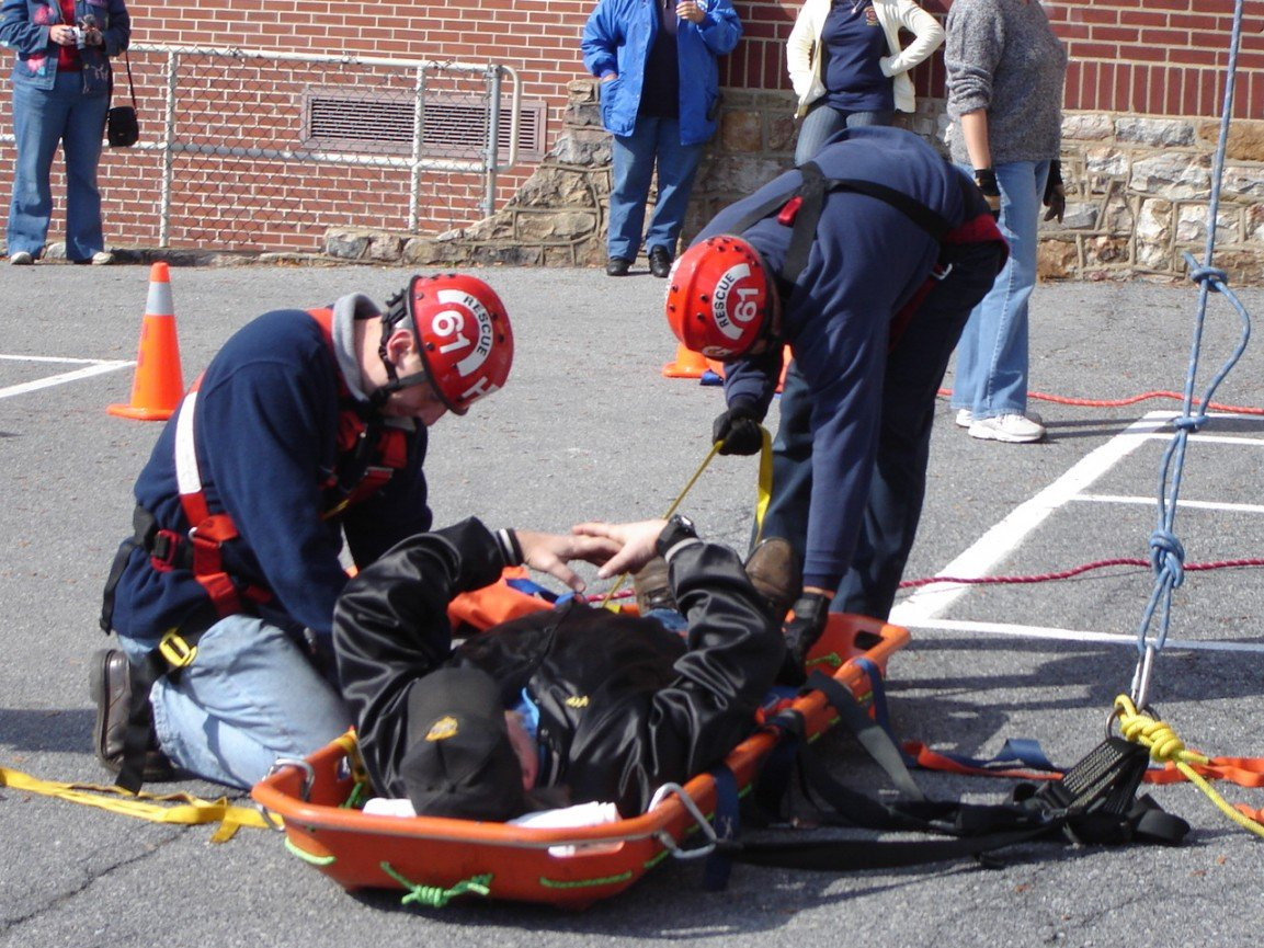 Captain Geschwindt and firefighter Frey demonstrate how to secure a victim into a stokes basket.